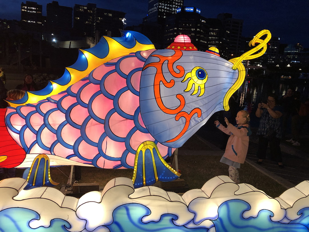 Small child shows delight at a large light-filled colourful fish sculpture