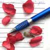 rose petals and a pen on lined paper