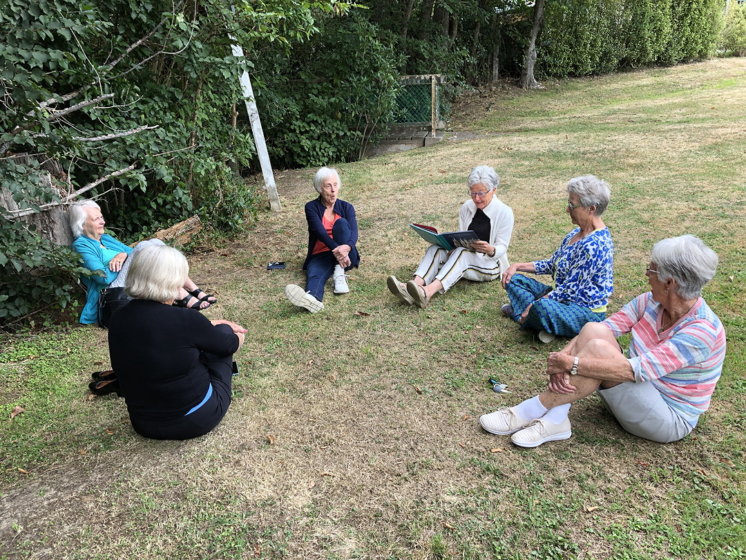 6 older women sitting on grass in a circle. One is reading aloud from a picture book.