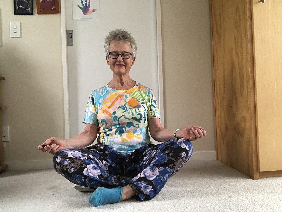 Photo of woman cross-legged on a carpet in meditation pose