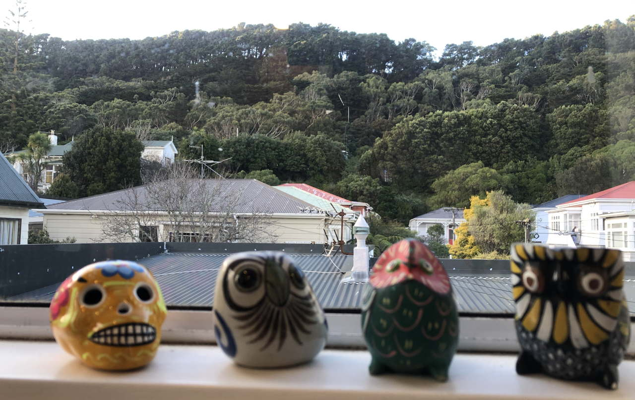 photo of 3 small decorative owl figurines and a Mexican plaster death skull