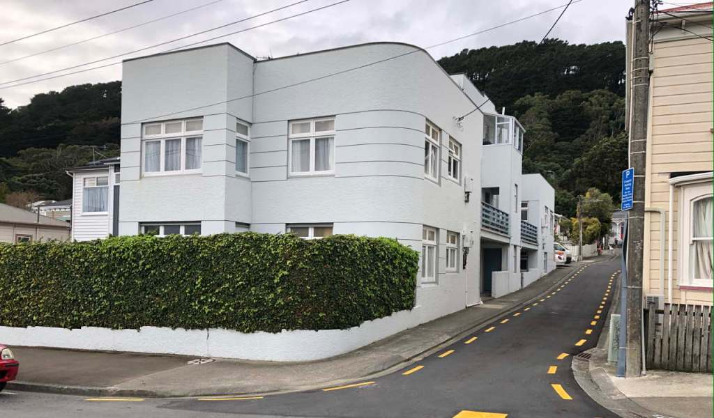 photo of art deco apartment block near a tree-covered hill