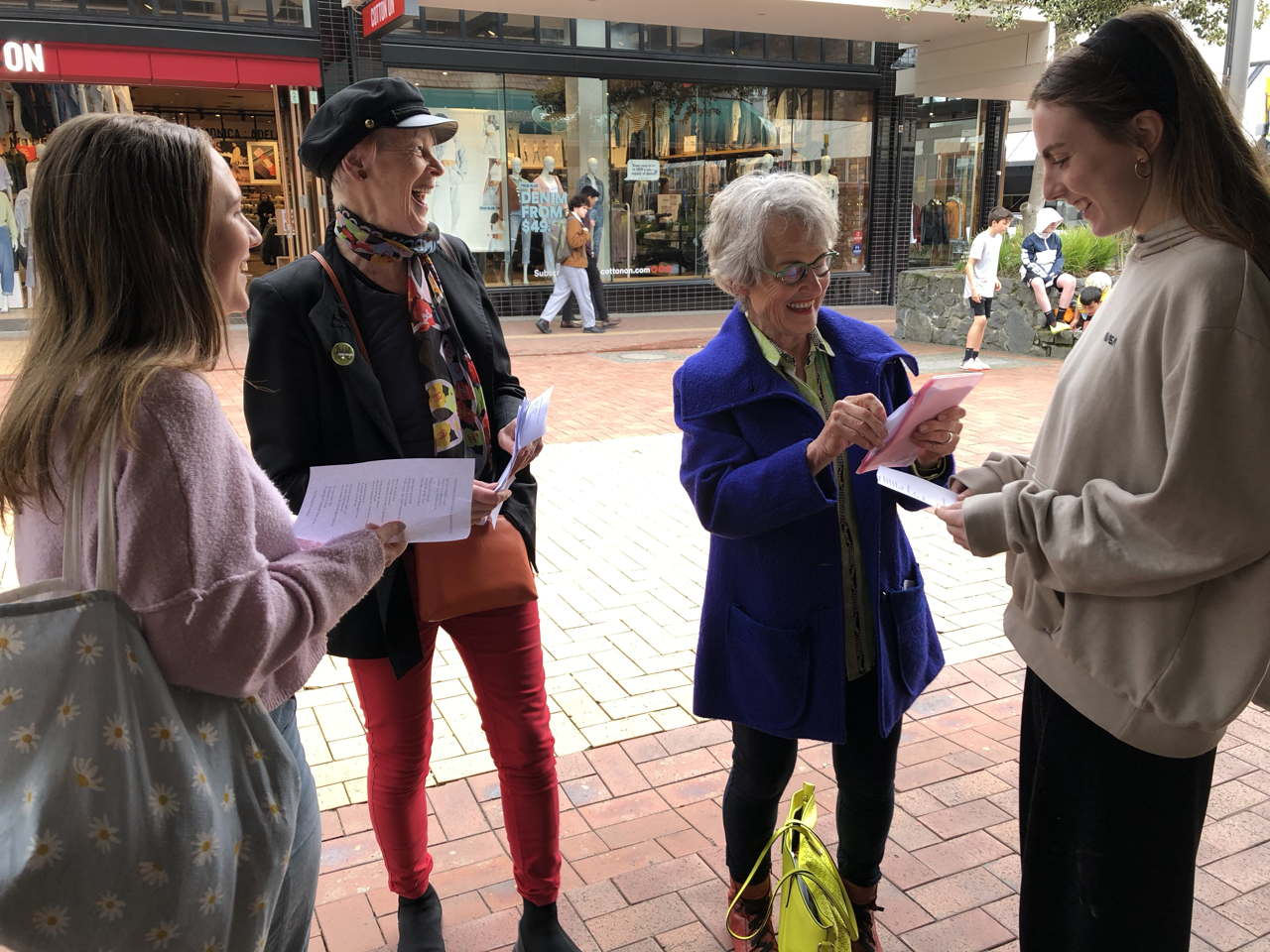 Two happy young women holding poems, two happy older women reading them
