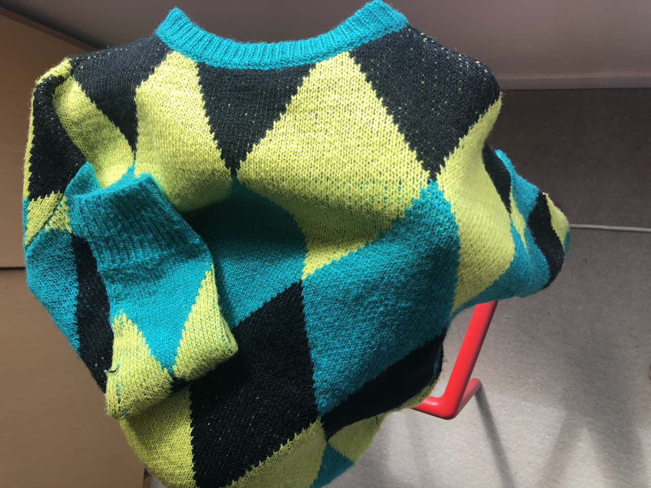 Photo of sweater in black, lime green and turquoise diamond shapes