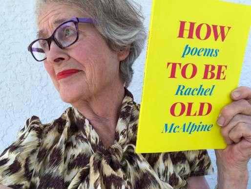 Worried woman holding a bright yellow and pink book called How To Be Old, Poems by Rachel McAlpine
