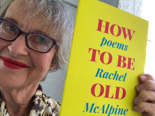Dishevelled woman holding a bright yellow and pink book called How To Be Old, Poems by Rachel McAlpine