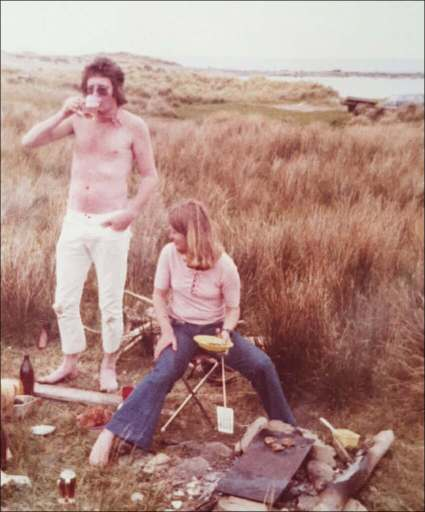Man standing bare chested drinking beer. woman in flared jeans barbecuing paua (?) patties. Wild grasslands and sea and rocks in the distance.