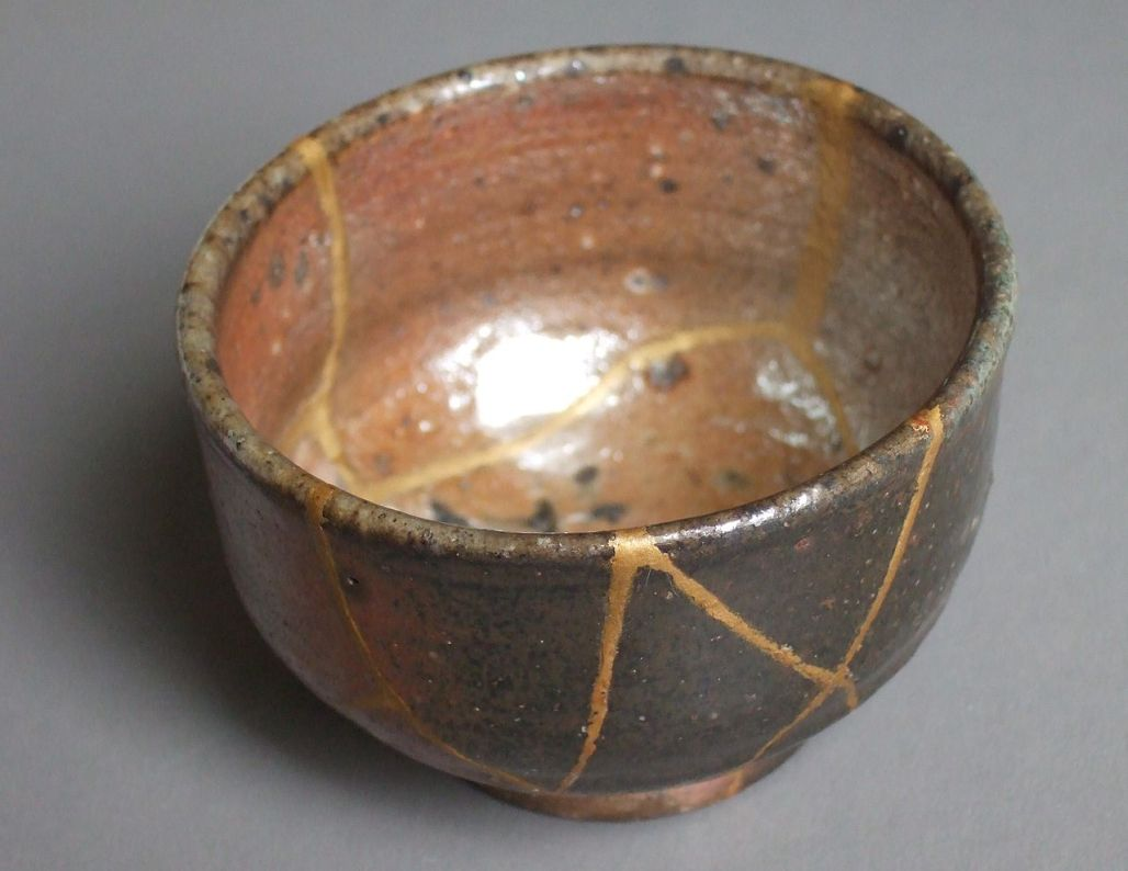A pottery bowl that has been broken and mended with gold lacquer along the break lines. Example of kintsugi, gold mending.