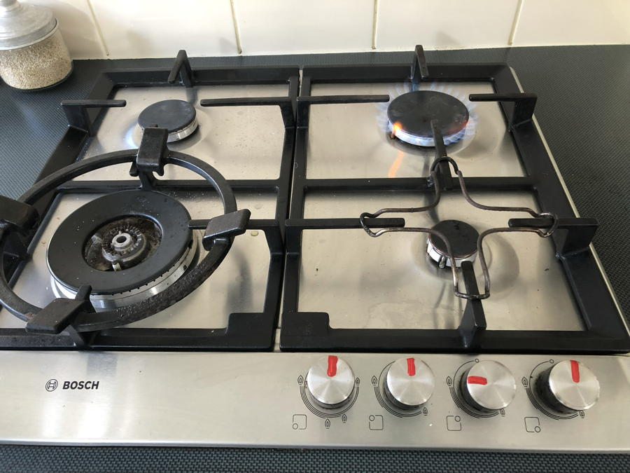 Photo of a gas stove-top with one ring alight. On-off knobs are clearly marked with red nail polish.