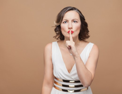 Woman showing shh secret sign. Emotional expressing woman in white dress, red lips and dark curly hairstyle. Studio shot, indoor, isolated on beige or light brown background.