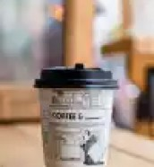 panda printed paper coffee cup on table