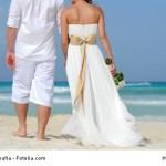 wedding couple walking away on the beach