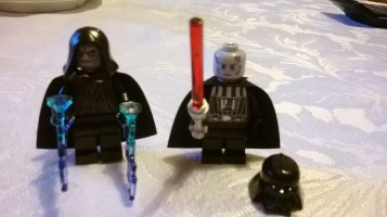 Emperor has grey, wrinkled head. Darth Vader has grey scarred head and comes with a lightsaber.