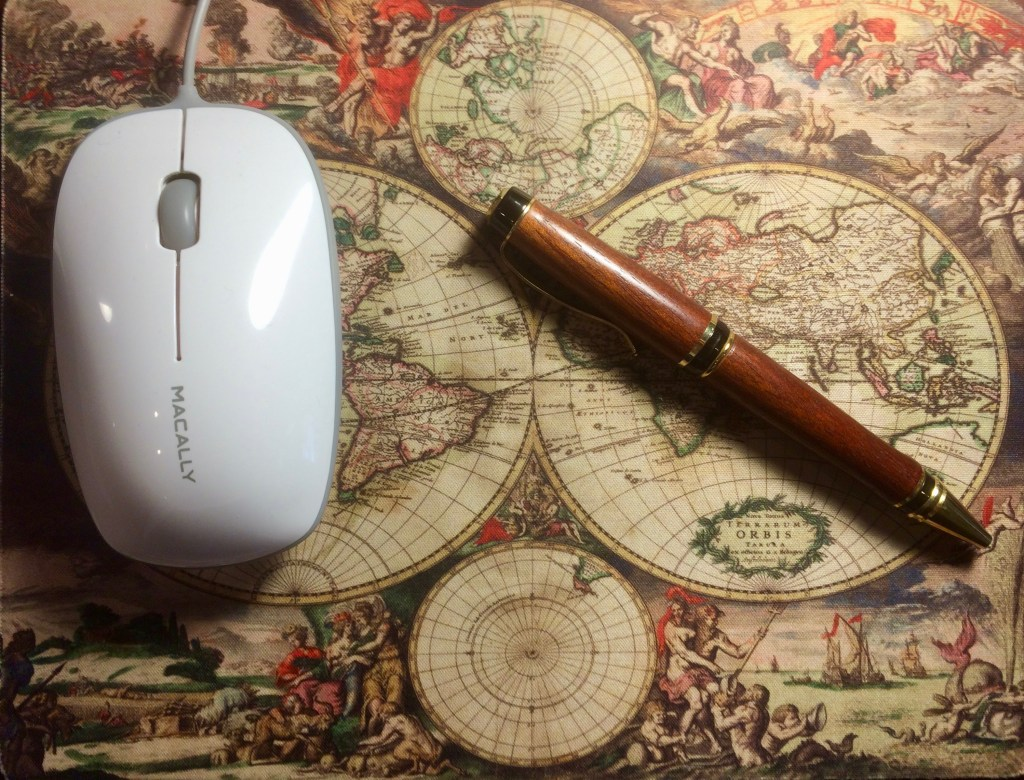 Beautiful wood pen on map of the world, next to computer mouse.