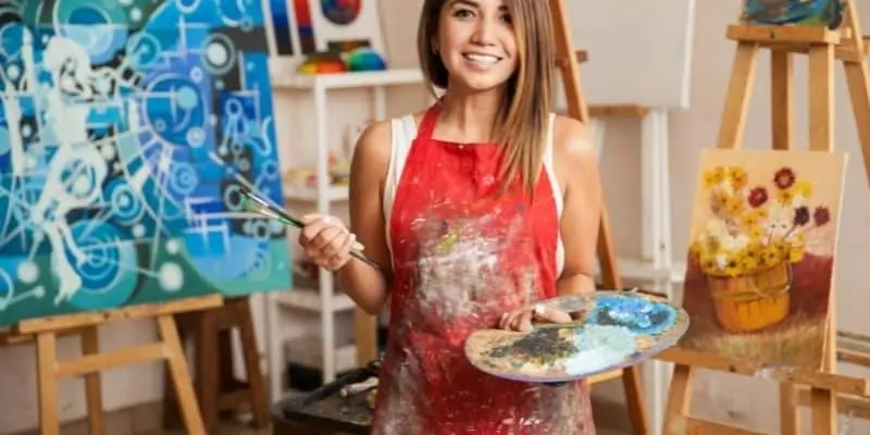 woman in pant smock with paint palatte