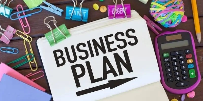 Business plan, paper clips, and calculator