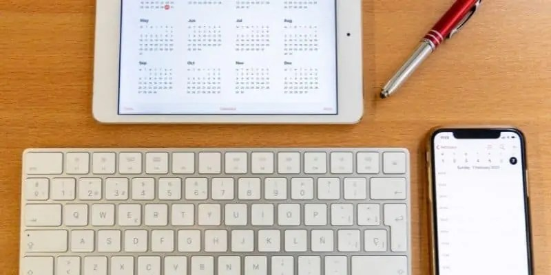 computer keyboard, pen, smartphone, and tablet with calendar