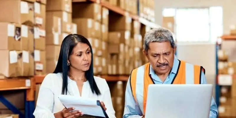 man and woman in shipping area with laptop