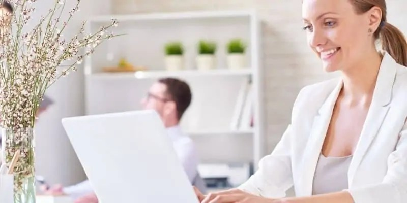 earn money by typing woman in white jacket typing in laptop