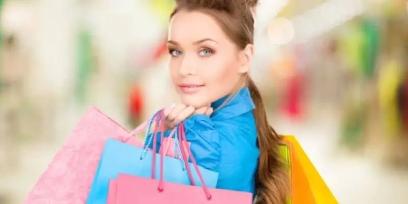 extra money for christmas woman in blue shirt with shopping bags