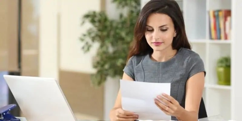 freelance writing cover letter woman in gray shirt at desk with letter
