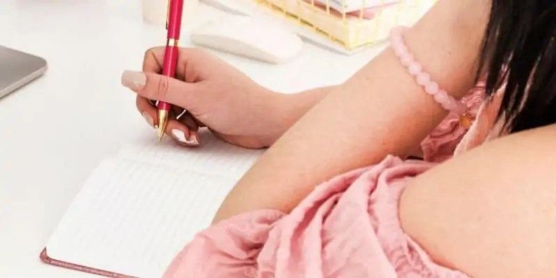 woman in pink shirt writing in a notebook