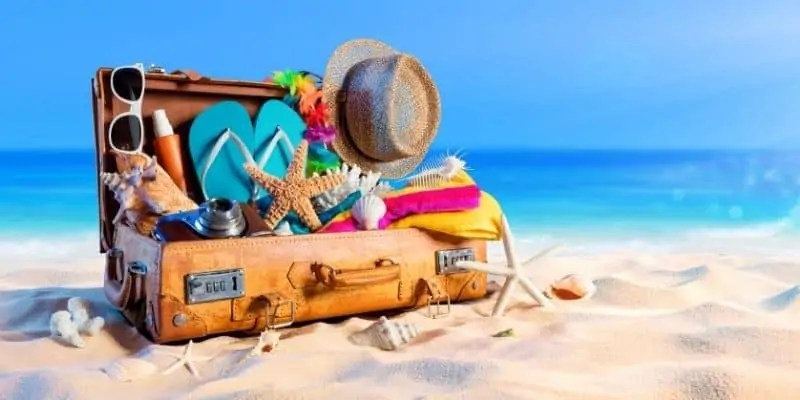 suitcase packed with flip flops, hate, seashells