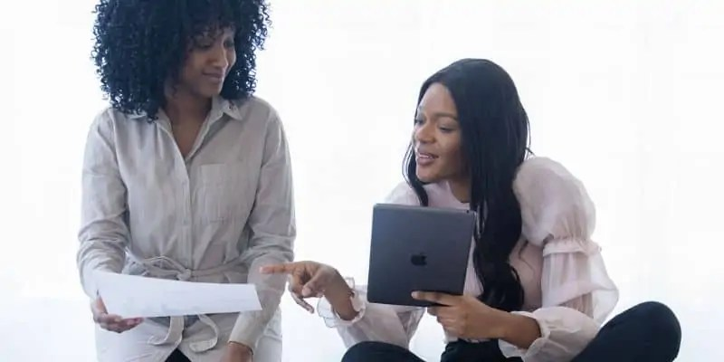 two women on tablet working and collaborating