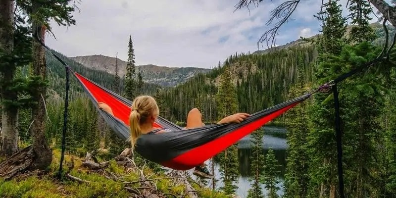 woman resting in a hammock on vacation so she can be more productive