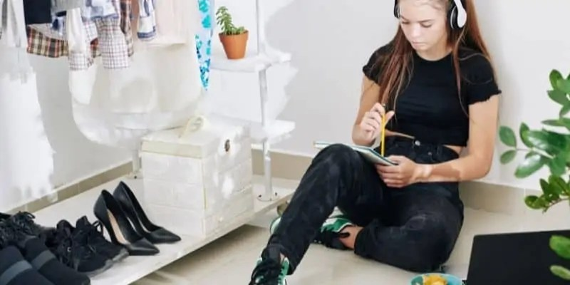 woman wearing all black and headphones writing in notebook