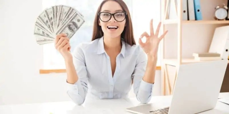 woman with glasses with a fan of money and laptop