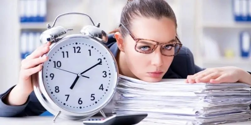 work from home successfully woman with head on stack of papers, crooked glasses and big clock