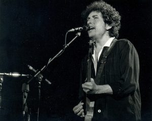 Bob Dylan singing and playing guitar