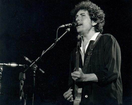 Bob Dylan singing and playing guitar