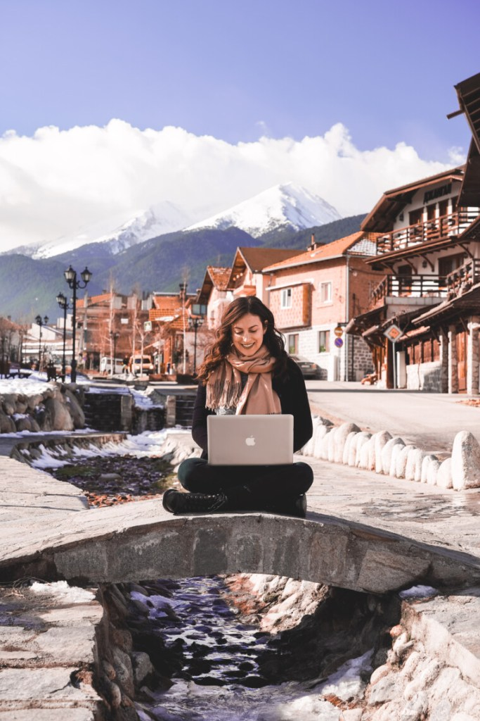 woman sitting outside on a tiny bridge working on her laptop in winter
