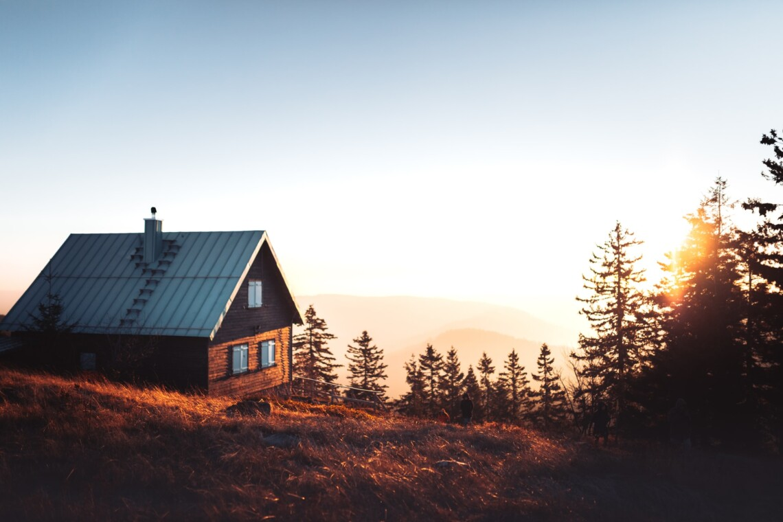A cabin sits amongst trees on a mountainside, with the sun setting in the background