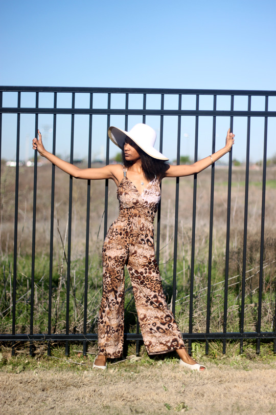 woman wearing leopard print clothing posing in front of a fence