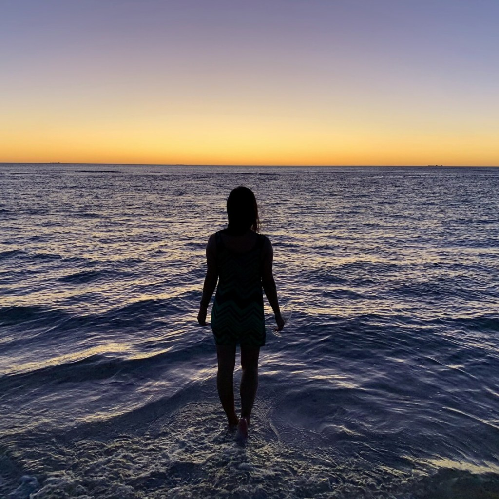 silhouet of a woman walking through the ocean at sunset