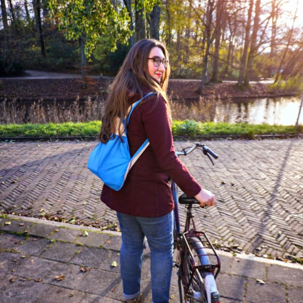 A woman (the author of this blog) stands outside at sunset holding her bicycle and wearing a Notabag on her back