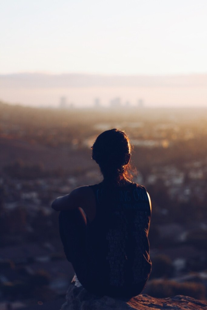 silhouet of a girl sitting against a blurry background
