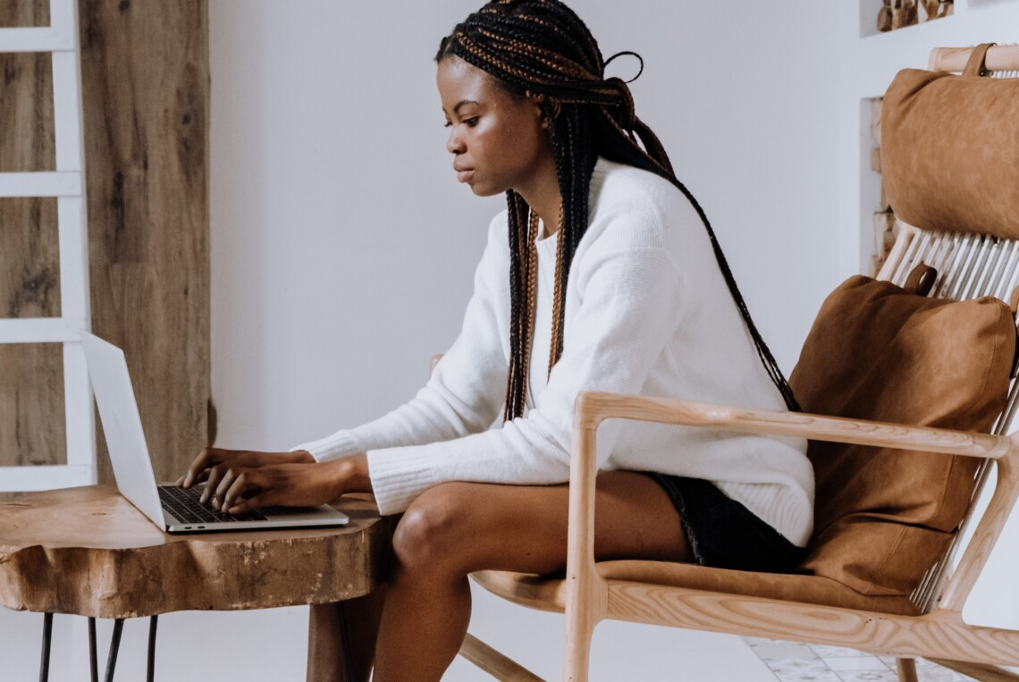 A Black woman sits in a hair on her laptop in a stylish apartment
