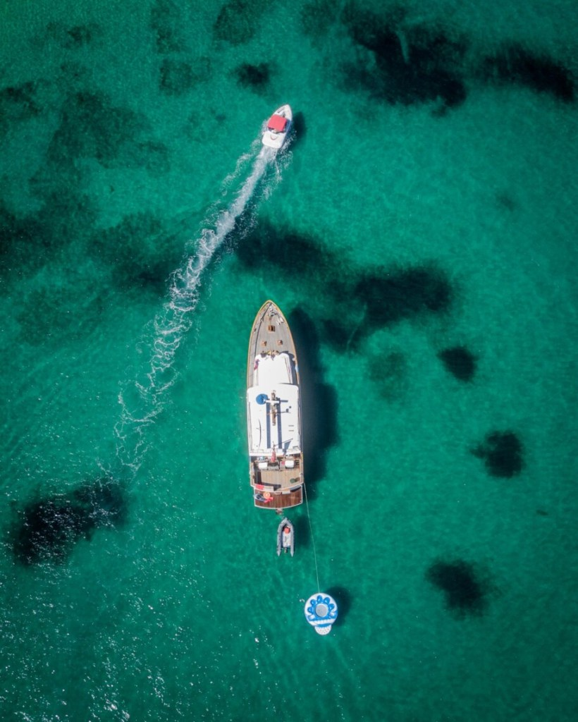 top down view of a yacht in clear water