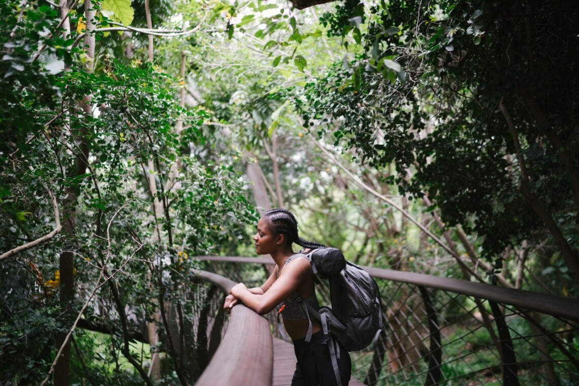 A Black woman stands on a bridge that curves through a forest. She is wearing a backpack and looking thoughtful