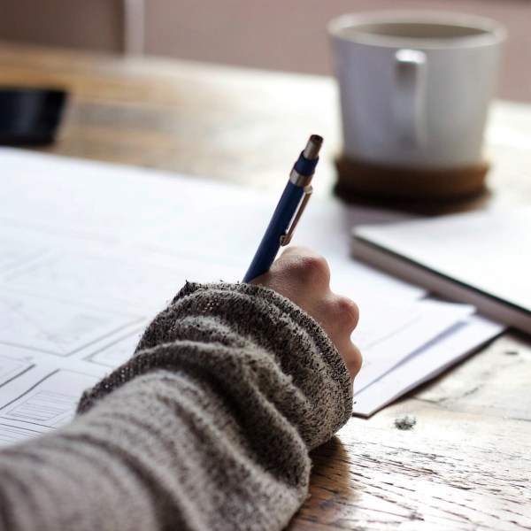 A woman's hand is writing on paper. There is a cup of coffee and the background is blurred
