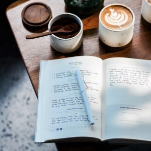 In the foreground, a notebook covered in writing sits open with a pen on the page. In the background there is a beautiful coffee