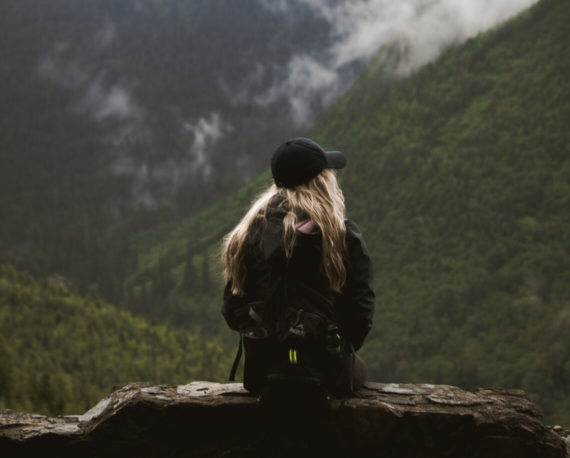 A woman sits with her back to the camera on a bench. Behind her are green mountains covered in fog. She looks thoughtful