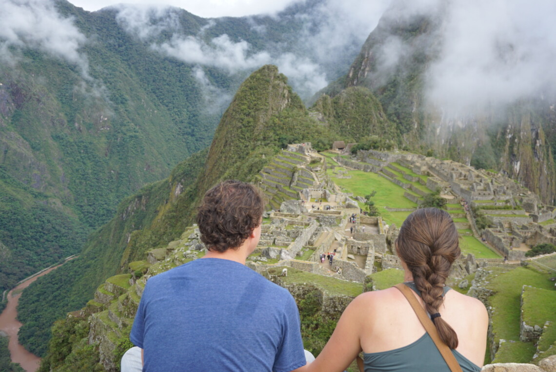 A woman and man (the ones who run this website) have their backs to the camera and are looking out at Machu Picchu. It's foggy and the clouds sit on top of the green mountains above the Incan ruins