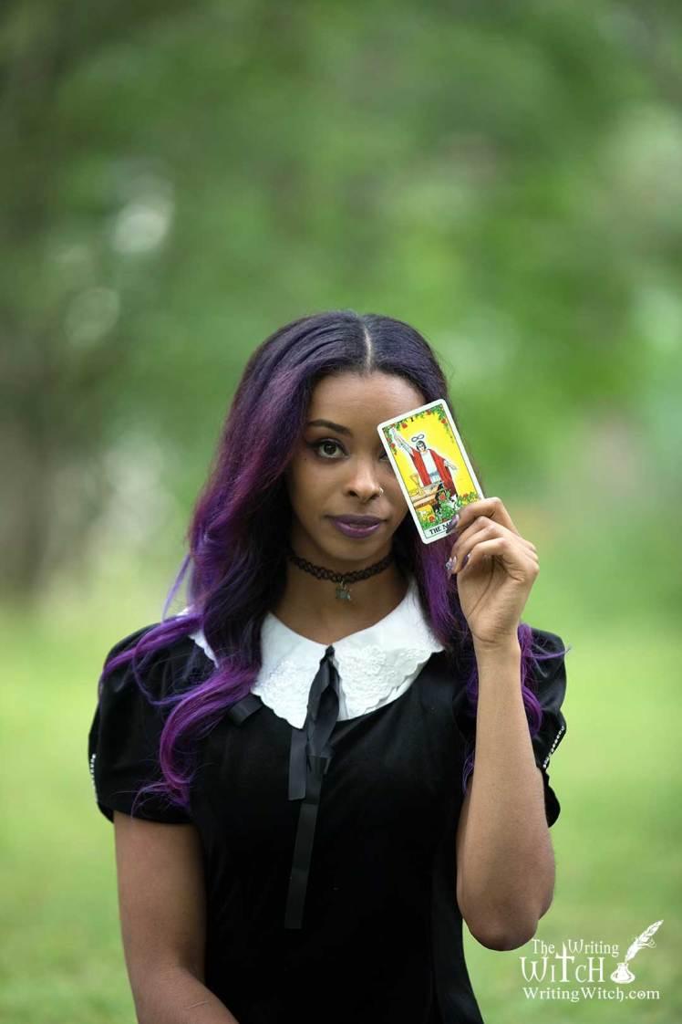 woman holding magician tarot card