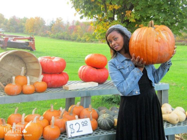woman holding a-pumpkin at a farm stand