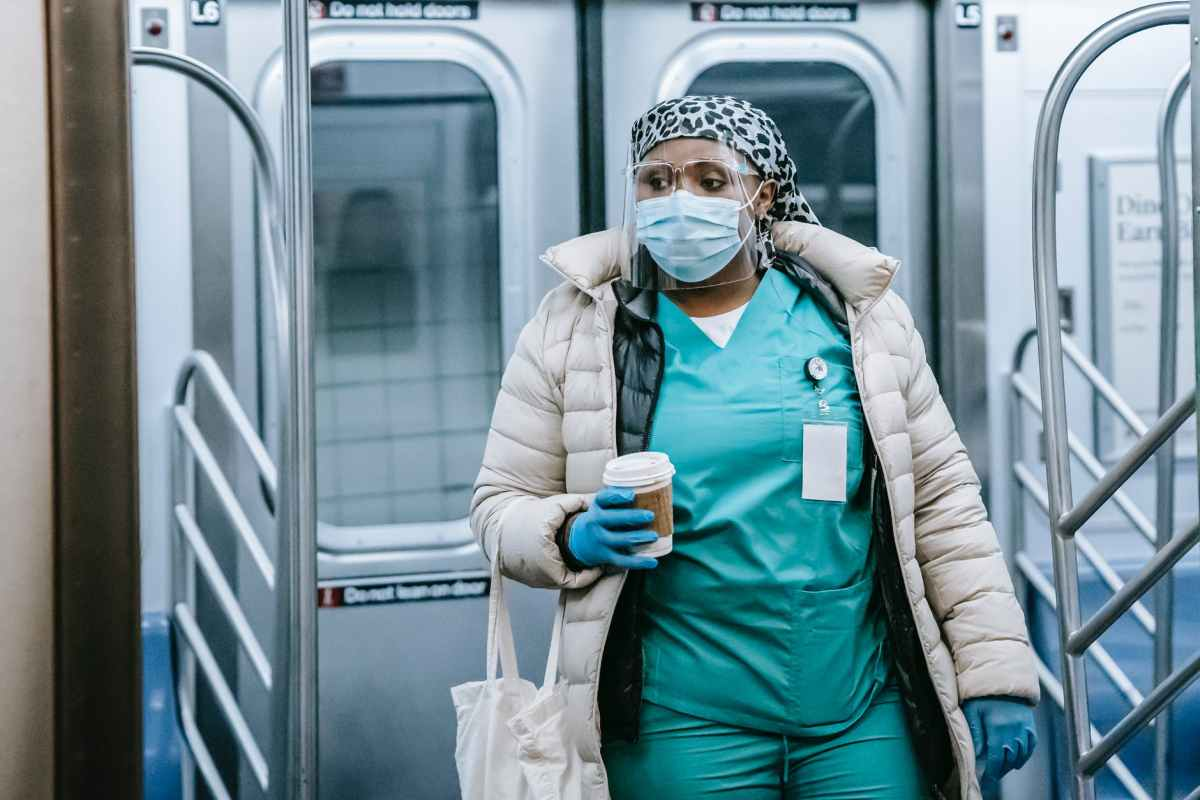 unemotional black nurse in mask leaving train in underground